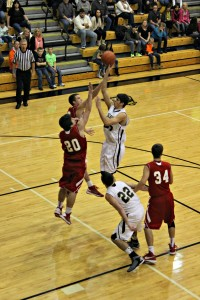 Senior Cole Murray soars over two opponents for 2 of his 25 points.  Delphi defeated the Hornets 50-44.