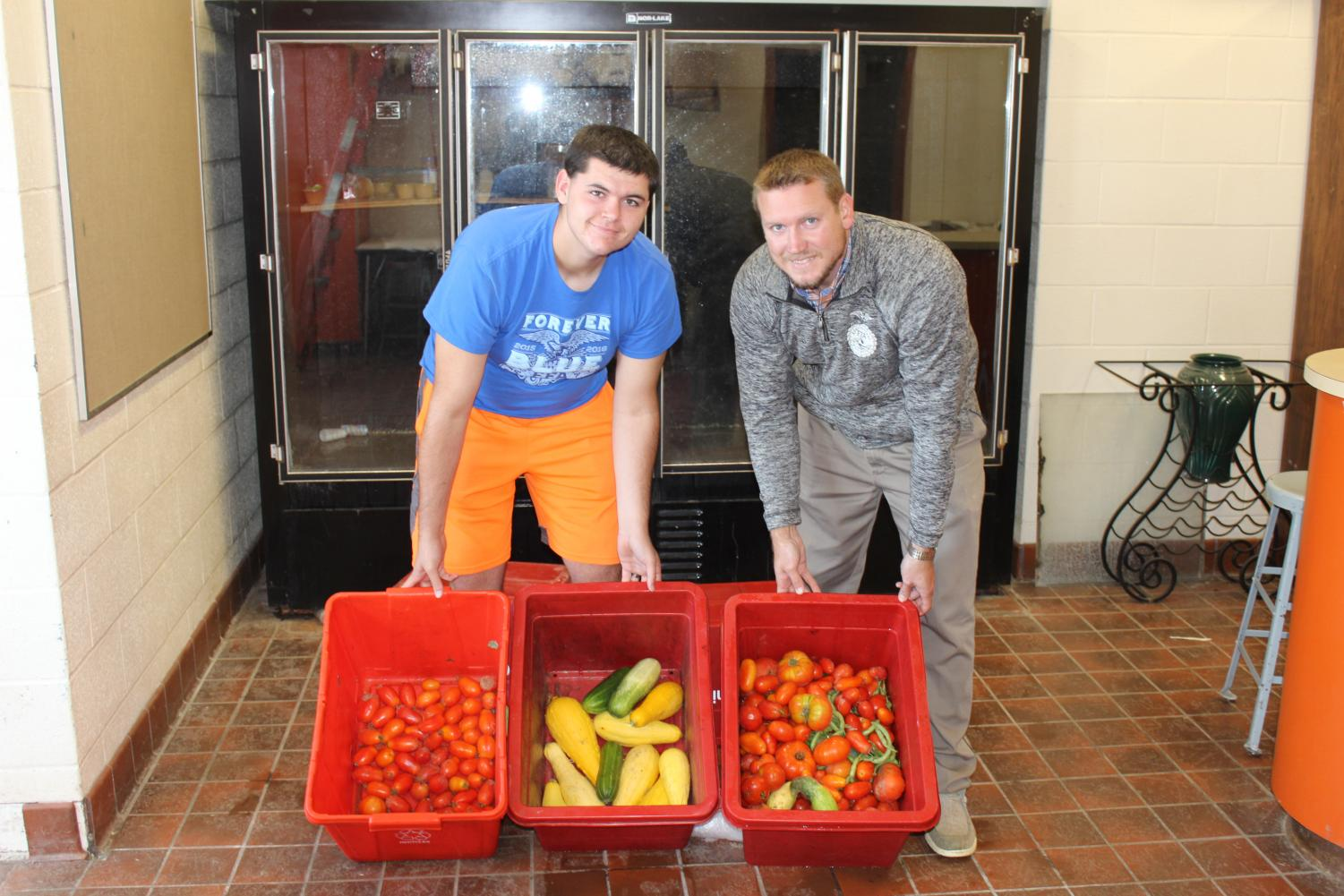 Jonas Brown, left, and Mr. Plank, right, show off this week's produce that was picked.