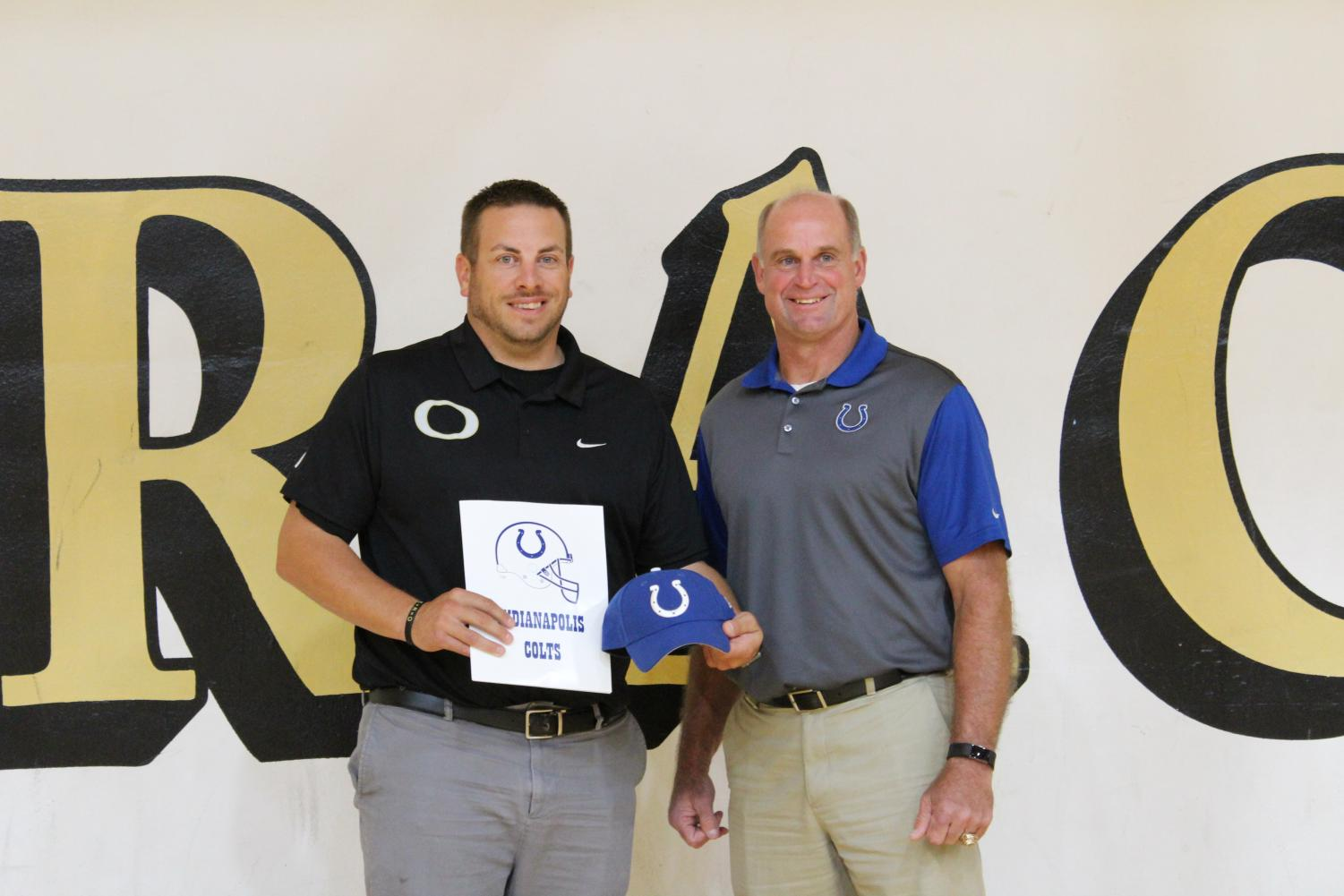 Mike Prior, former Super Bowl champion, presents Strasser with the Colts' Week 7 Coach of the Week award