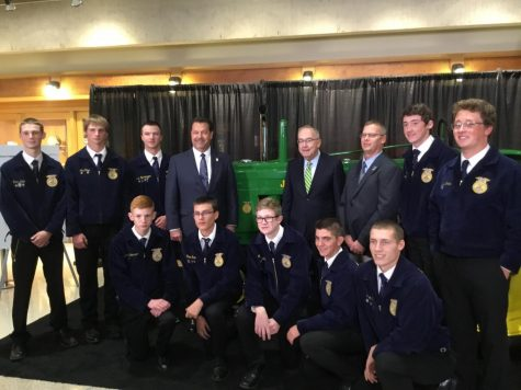 Delphi presents a 1945 John Deere B tractor to John Deere on behalf of National FFA with the CEO of National FFA and the CEO of John Deere present.