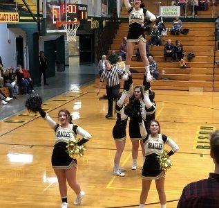 Cheerleaders prepare stunts for basketball games
