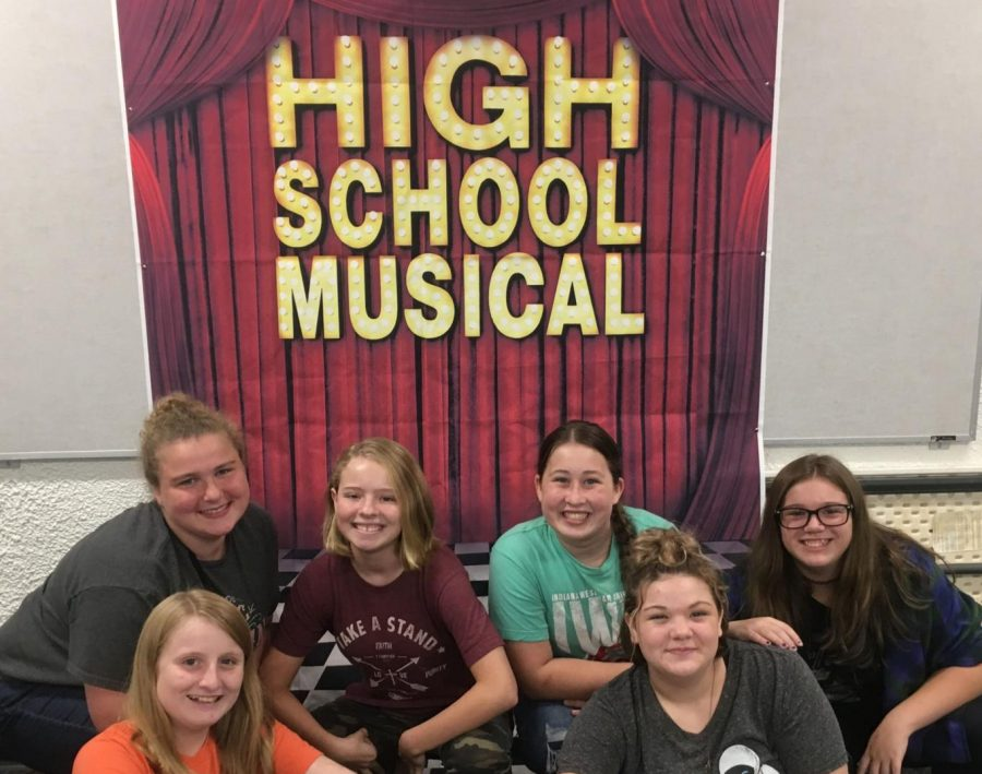 Some members of Drama Club pose in front a sign advertising the musical.