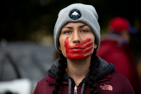 A Native American woman with the symbolic MMIW hand print