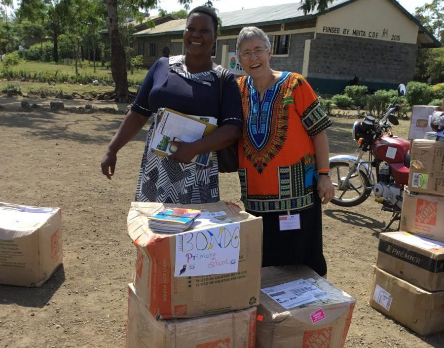 Sharon Allen (r), an African Library Project Volunteer, poses in front of books sent from the Delphi Interact club, with the Bondo Township Primary School librarian (l).