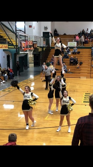 Cheerleaders prepare stunts for basketball games