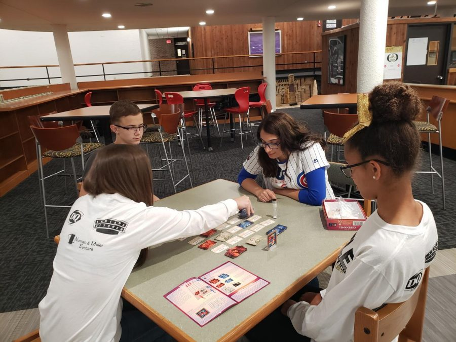 Students gather around the table to play a board game. Game Club meets in Mr. Gaspars room after school on Thursdays.