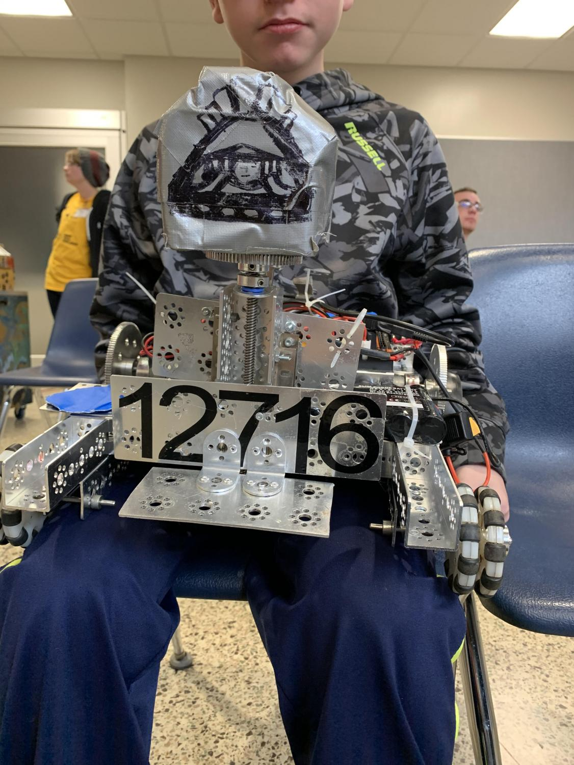 Freshman Eric Achor holds Delphi's robotics team's robot at a recent competition.