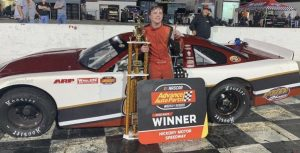 Sam Butler standing by his car after his win.